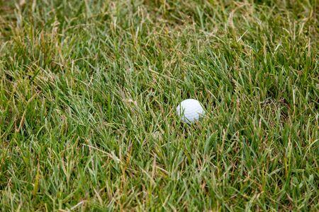A white golf ball lies in rough, taller grass off the fairway on a golf course. Stock Photo