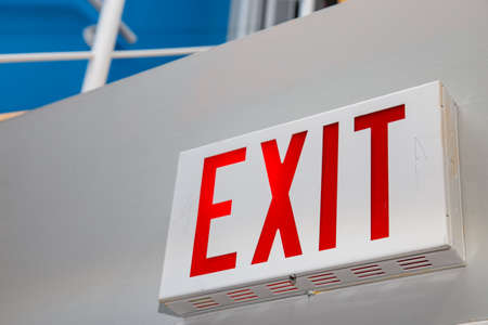 "A perspective view from a low angle showing a red ""EXIT"" sign on a white wall."