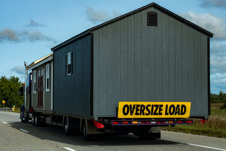 Two pre-built garden sheds are being transported by a semi-trailer transport truck on a highway, with a sign on the back indicating an oversize load.