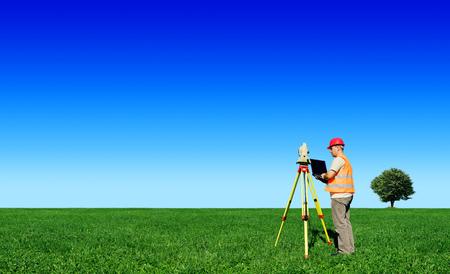 Surveyor on green field, blue sky in background
