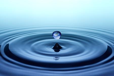 Gota de lluvia con la imagen de la tierra cayendo sobre la superficie del agua suave