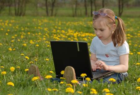 Cute blonde girl with a laptop on green flowery meadow