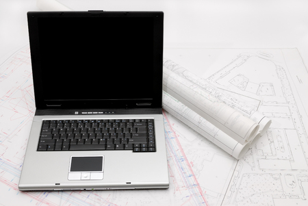 Computer with architectural plans lying on table