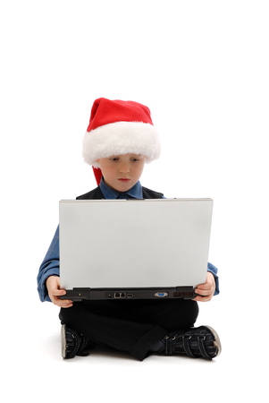 Little boy in Santa Claus cap with a laptop on white background, isolated Archivio Fotografico