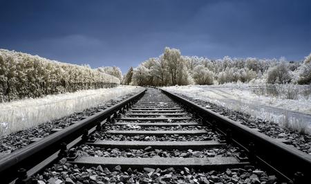 Landscape, view along the railway tracks seen through an infrared filter