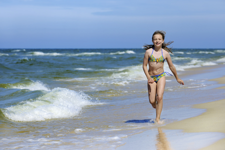 Cute little girl in swimsuit running on the beach, the blue sky in background Zdjęcie Seryjne