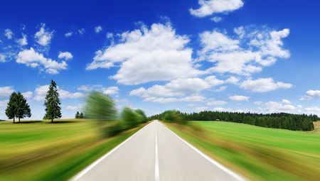 Road among green fields with motion blur effect, blue sky and white clouds in the background Banco de Imagens - 118132364