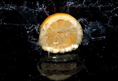 Lemon falling into water and causing splash. Black background.