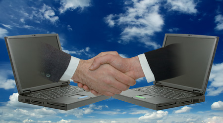 Businessmen handshake. Two male hands emerging from laptops. Blue sky and white clouds in background 스톡 콘텐츠