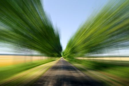 Road among green fields with motion blur effect, blue sky in the background Banco de Imagens - 118132695