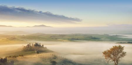 Panorama, Italian beautiful landscape, foggy rolling fields of Tuscany in light of the rising sun Standard-Bild