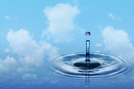 Drop of rain with earth image falling on smooth water surface. Blue sky and white clouds in background.