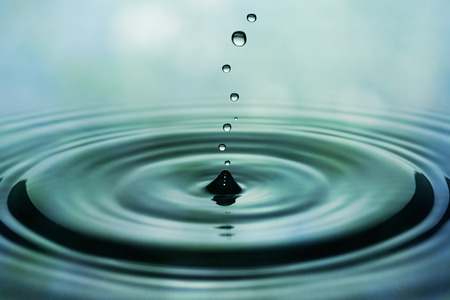Drops of rain falling on smooth water surface. Green blurred pattern in background.