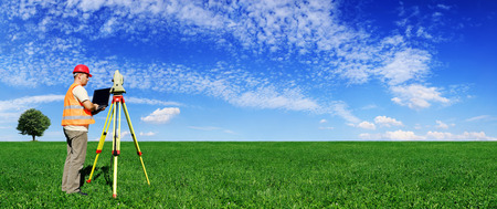 Surveyor on green field, blue sky and white clouds in background