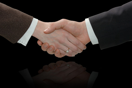Handshake of businessman and businesswoman. Isolated on black background.