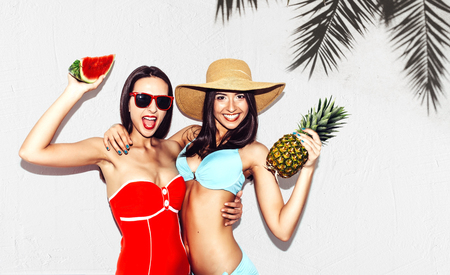 ni�as gemelas: Vacation. Summer travel. Two beautiful sexy brunette twin girls outdoor with watermelon and pineapples in bikini on white wall background with palm tree shadow having fun laugh smile at the beach