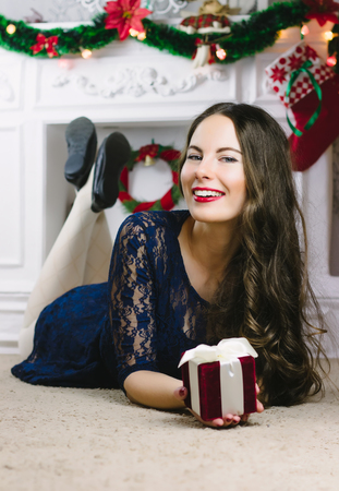 christmas manicure: Christmas Woman. Beauty Model Girl with Fireplace on Background. Christmas Gift in Hand. Open Mouth Beautiful Teeth Smile. True Emotions. Red Lips and Manicure. Beautiful Holiday Makeup. Not isolated