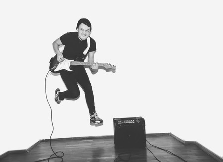 headbanging: Awesome crazy fashion young musician rock guitar player jumps with passion in studio. Stylish rocky emotional man. Black and white toned.