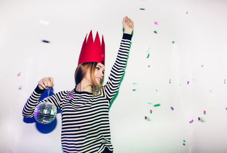 Party girl in colorful spotlights and confetti smiling on white background celebrating brightful event, wears stripped dress and red crown. Sparkling confetti, having fun, dancing, laugh, disco ball. Stock Photo