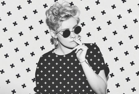 Contrast pattern stylish fashion sexy blonde bad girl in a black t-shirt and rock sunglasses. Dangerous rocky emotional woman. white toned. background, not isolated