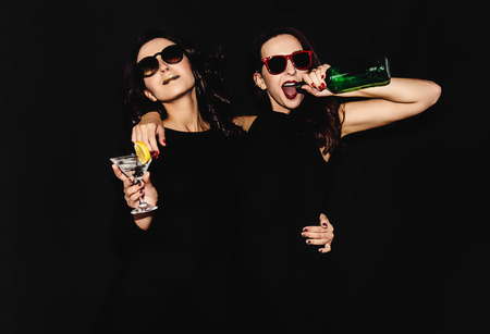 rumour: Two beautiful women black night fashion dress posing isolated on a black background. Pretty brunette girl friends twins having fun drinking cocktails. Singing and dancing. Bottle glass of alcohol. Stock Photo