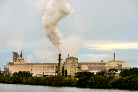 man made structure: A riverside factory  photographed in the late afternoon  with a smoke stack emitting a large cloud of smoke into the sky