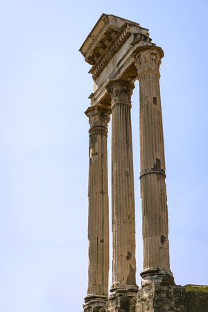 An ancient Roman ruin with three eroded columns standing as a testament to the strength of early architecture photographed against a clear blue sky