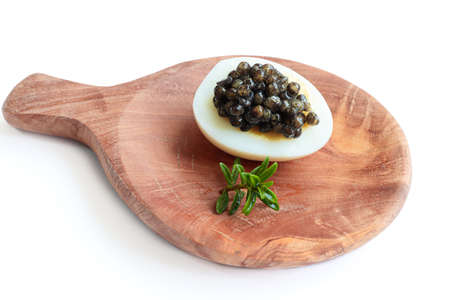Gourmet dish, delicious black sturgeon caviar on a quail egg with rosemary on the wooden plate isolated on the white background