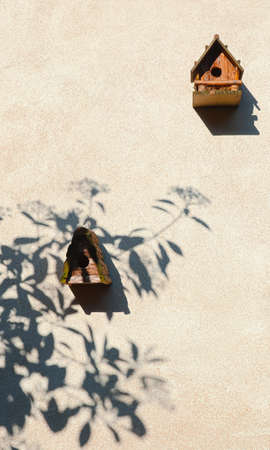 Two wooden handmade birdhouses and tree shadow on a light cement wall, nature protection and lifestyle concept