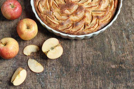 Traditional french homemade apple pie in a white ceramic baking form and autumn apples on old dark wooden background. Top view, copy space