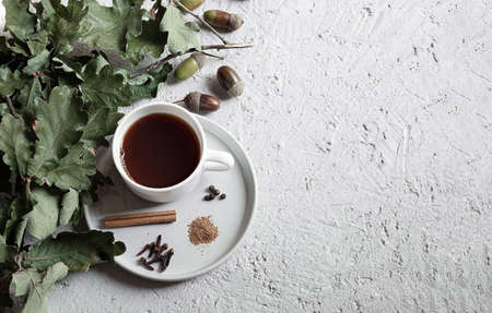Cup of acorn coffee, acorns and green oak leaves on a gray background. An alternative to traditional coffee, a healthy homemade eco-friendly hot drink without caffeine. Flat lay, copy space