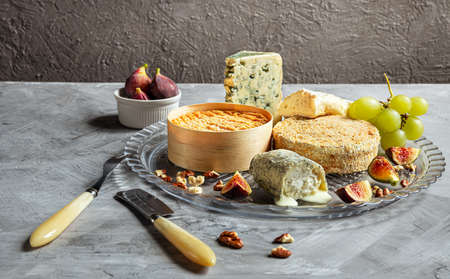 Assortment of French cheese - camembert, roquefort, brie, goat cheese and epoisse with grapes, figs and nuts on a gray background Reklamní fotografie