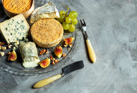 Assortment of French cheese - camembert, roquefort, brie, goat cheese and epoisse with grapes, figs and nuts on a gray background. Top view with copy space