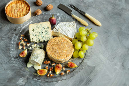 Assortment of French cheese - camembert, roquefort, brie, goat cheese and epoisse with grapes, figs and nuts on a gray background. Top view, copy space Reklamní fotografie