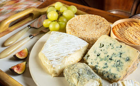 French cheese - camembert, roquefort, brie, goat cheese and epoisse with grapes and figs close-up