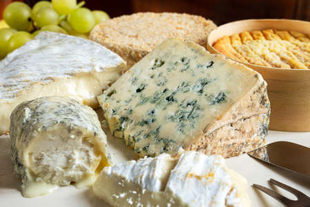 French cheese - camembert, roquefort, brie, goat cheese and epoisse with grapes close-up