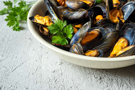Delicious fresh steamed mussels in white wine sauce with parsley in a white plate on a gray background close-up 免版税图像