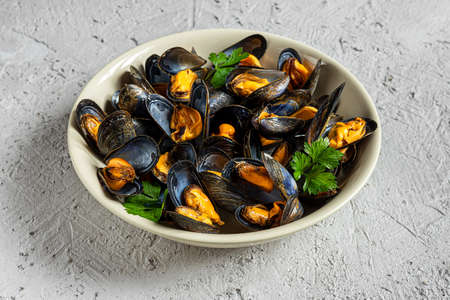 Delicious fresh steamed mussels in white wine sauce with parsley in a white plate on a gray background