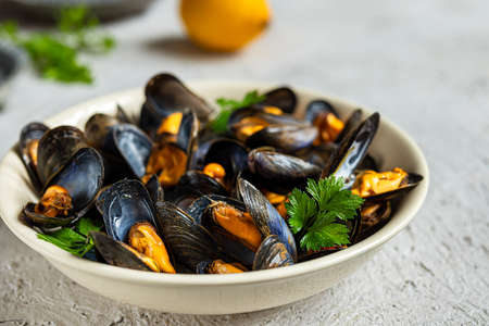 Delicious fresh steamed mussels in white wine sauce in a white plate, a lemon and parsley on a gray background