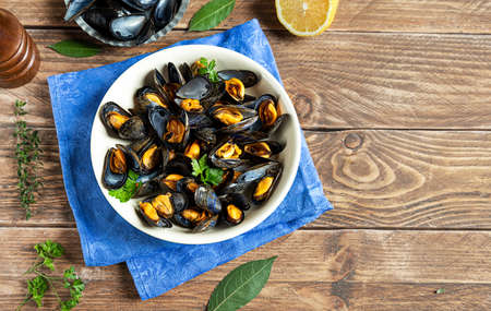 Delicious fresh steamed mussels in white wine sauce with parsley in a white plate on a wooden table