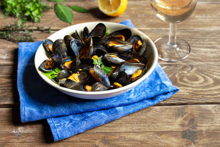 Delicious fresh steamed mussels in white wine sauce in a white plate, a lemon, parsley and a glass of wine on a wooden table
