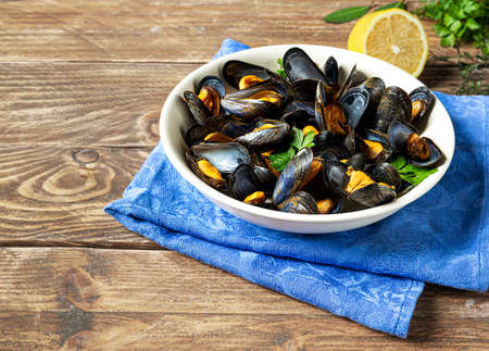 Delicious fresh steamed mussels in white wine sauce in a white plate, a lemon and parsley on a wooden table 免版税图像