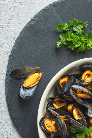 Delicious fresh mussels steamed according to a traditional french recipe in a white wine sauce with parsley in a white plate on a gray background 免版税图像
