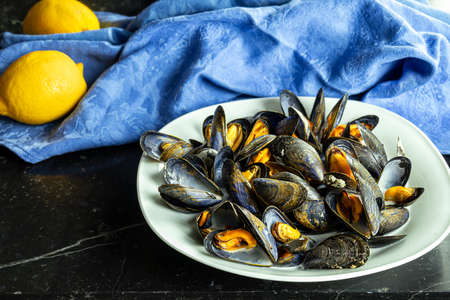 Delicious fresh steamed mussels in white wine sauce in a white plate and a lemon on a dark gray background