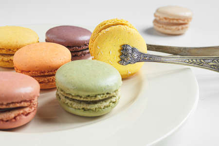 Classic french macaroons of different colors on a light plate and vintage silver serving tongs on a white table, close-up