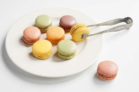Traditional french macaroons of different colors on a light plate and vintage silver serving tongs on a white table