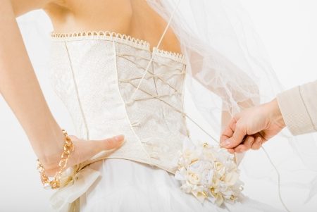 Maid  helping the bride with her dress  Stock Photo