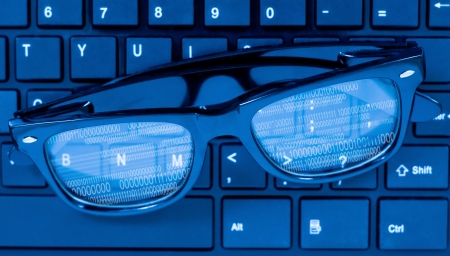 Glasses on laptop computer keyboard with numbers reflecting on it