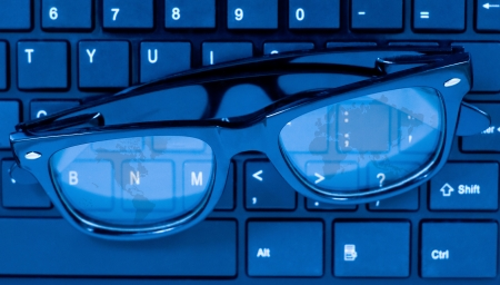 Glasses on laptop computer keyboard with world map reflection on it photo
