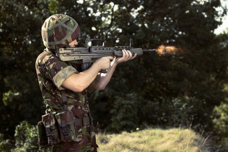 military man: Young soldier with gun shooting Stock Photo